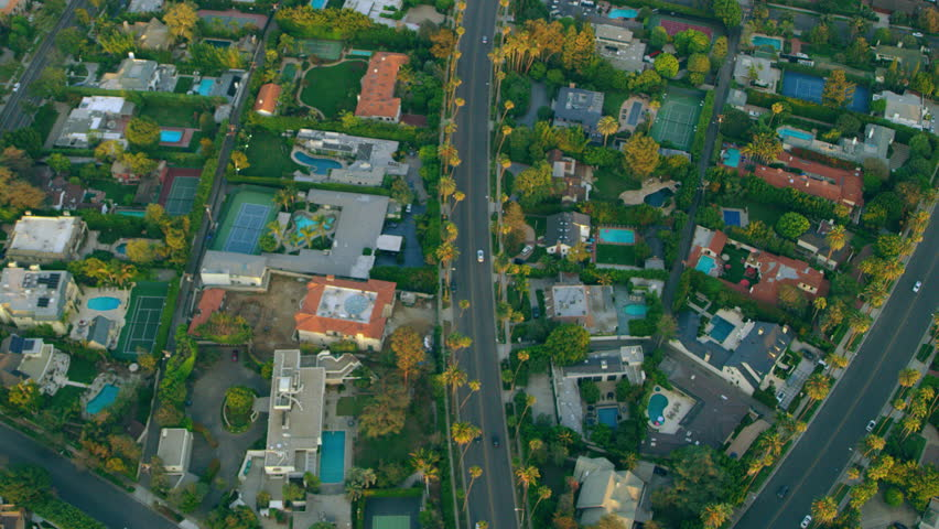 Flying over Wilshire Boulevard in Los Angeles, palm trees, beautiful homes, while sun sets. Medium close shot with a RED camera.