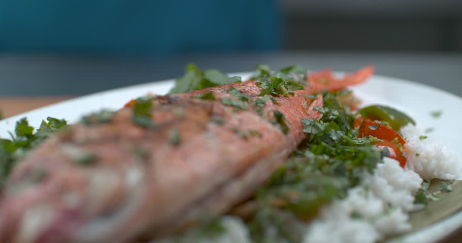 Fresh dill dropped onto a plate of freshly cooked fish, rice and salad in soft focus, slow motion, in soft light. Closeup in 4k Phantom Flex camera