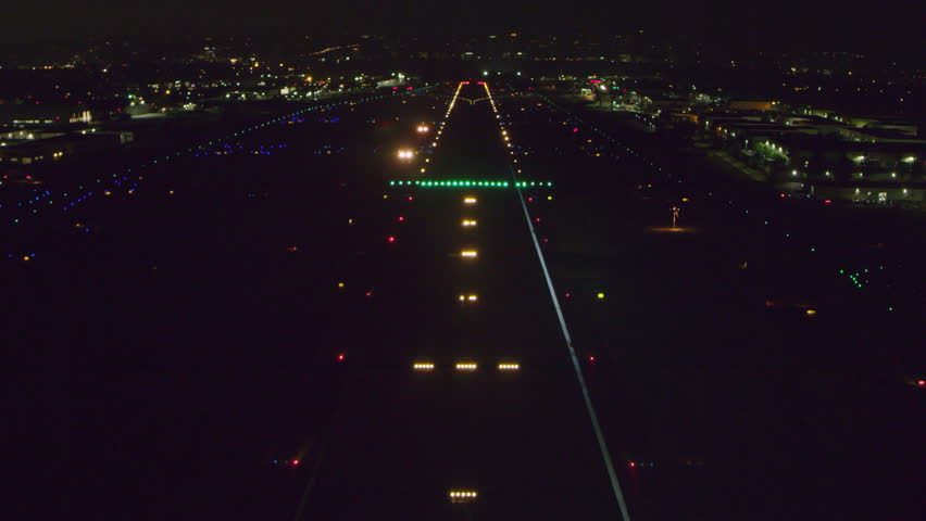 Aerial POV view landing on a runway on a clear night in Los Angeles, California. Shot on 4K RED camera.