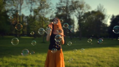 Beautiful young redhair girl blowing soap bubbles outdoors. Slow motion shot of childhood time in adult age. Fun under the rays of the sun. Sunrise. Focus on bubbles.