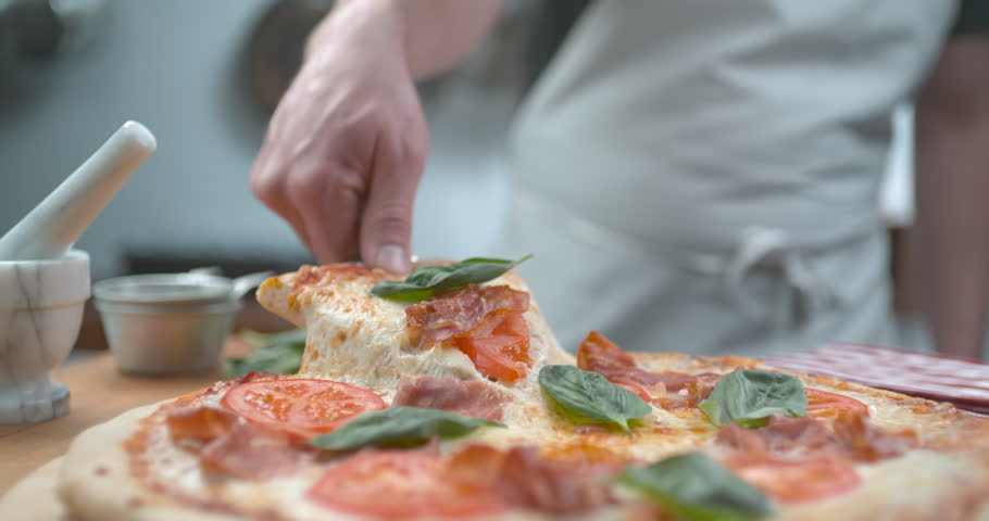Freshly baked thin crust pizza being sliced with melty cheesy closeup ultra slow motion with 4k Phantom Flex camera.