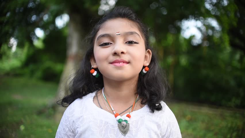 A cute little Indian girl is smiling and agrees to something, approves something, saying yes, happy little girl, Slow motion