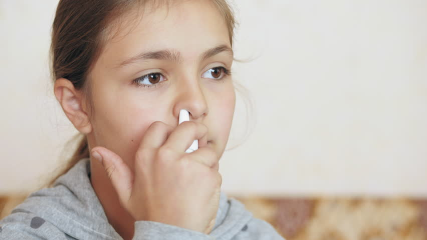 Teen girl sprays into the nose spray, home treatment.   Shutterstock HD Video #1019075806