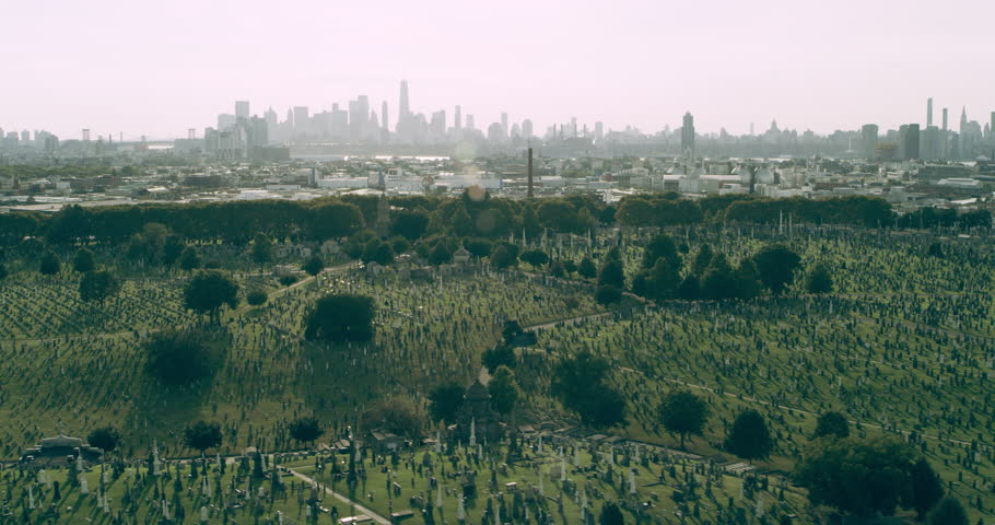 Aerial view of green cemetery with Manhattan skyline in distance in New York during the day under blue skies. Wide shot on 4K RED camera.