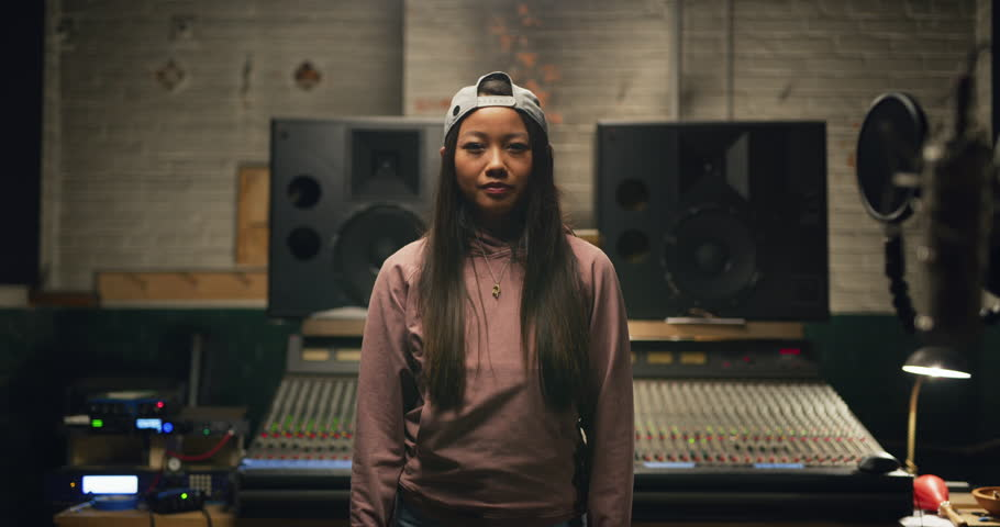 Portrait of young millennial Asian woman with long hair and backwards baseball cap in pink hoodie and jeans in front of professional mixing boards in studio. Medium shot on 4K RED camera.