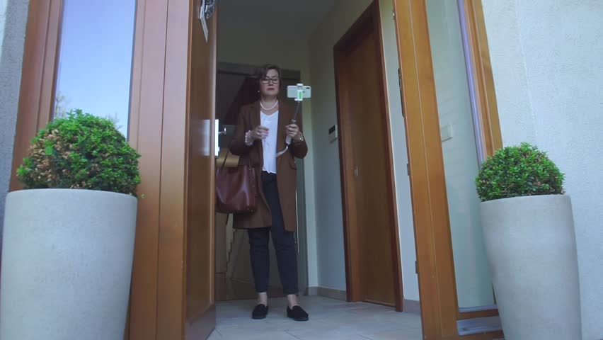 Realtor blog content maker woman looks into the phone at the door of property wish to sell. She took photos and videos of the house for sale.  Preparing a presentation for customers. Royalty-Free Stock Footage #1019088601
