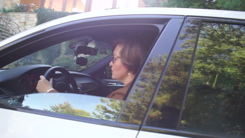 Woman vehicle blogger looks out of the white automobile. She got a car for a test drive. Her customer will receive a competent review in the form of a blog article.
