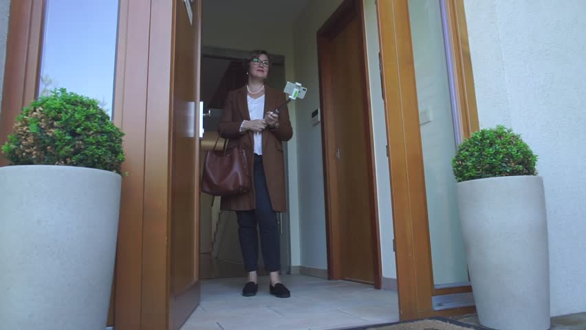 Mature woman in brown clothes stands in the doorway with smartphone selfie stick and shooting blogger podcast about career opportunities of internal auditor project manager. Vlogger concept.