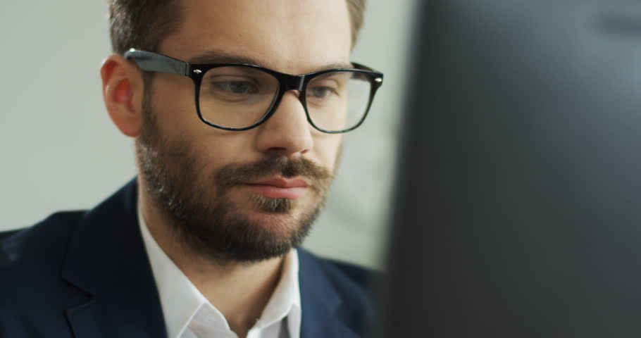 Close up of the Caucasian good looking young man in glasses with serious face working at the computer. Portrait. Inside. #1019094385
