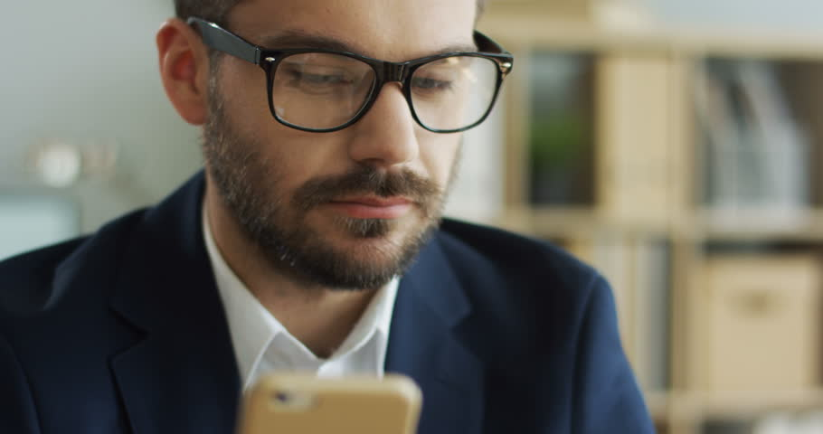 Close up of the young Caucasian man in business style and glasses shopping online on the smartphone with a credit card and being happy. Portrait. Inside. #1019094445