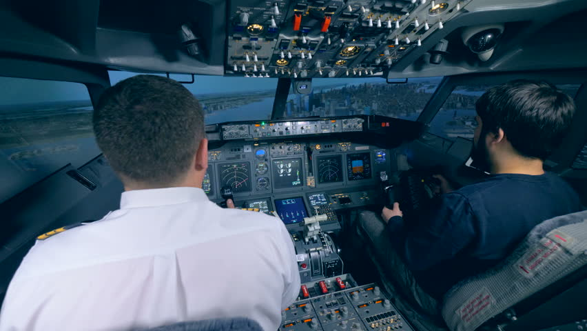 Male pilots sit in a cockpit of a flight simulator, close up. | Shutterstock HD Video #1019101216
