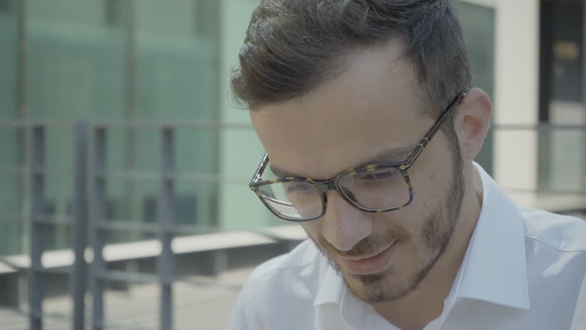 Serious Caucasian agent in glasses working outside. Busy white collar specialist focusing on task. Close up shot. Smart worker concept | Shutterstock HD Video #1019102176