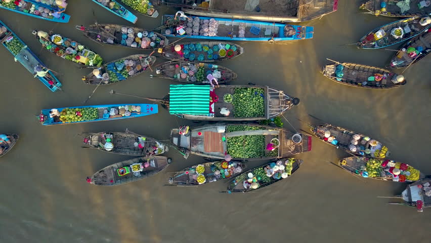 DRONE, TOP DOWN: Flying above local people doing business on the colorful floating market set on the calm murky river in the scenic Vietnamese countryside. People doing business on their wooden boats. Royalty-Free Stock Footage #1019108749