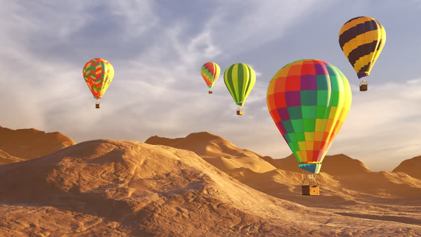 Colorful hot air balloons flying over mountains and desert landscape during sunset. Five large multi-colored balloons slowly rising against a beautiful cloudy sky. Travel, adventure, festival.