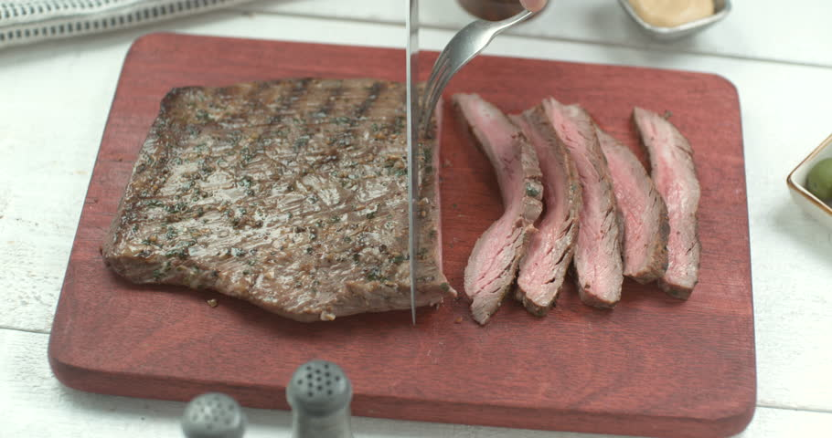 Grilled beef tenderloin cut in slices with a big kitchen knife and fork with salt, pepper and condiments around. Close shot 4K  Phantom Flex camera. Chef's Table and cooking show inspired footage