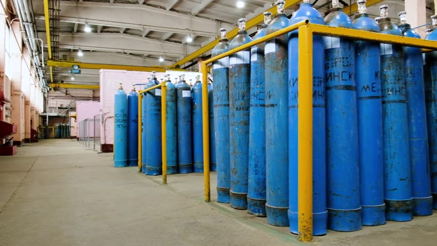 A bundle of oxygen cylinders with compressed gas secured on yellow skids in platform. Blue Oxygen tanks for industry. Liquefied oxygen production. Factory Royalty-Free Stock Footage #1019149381