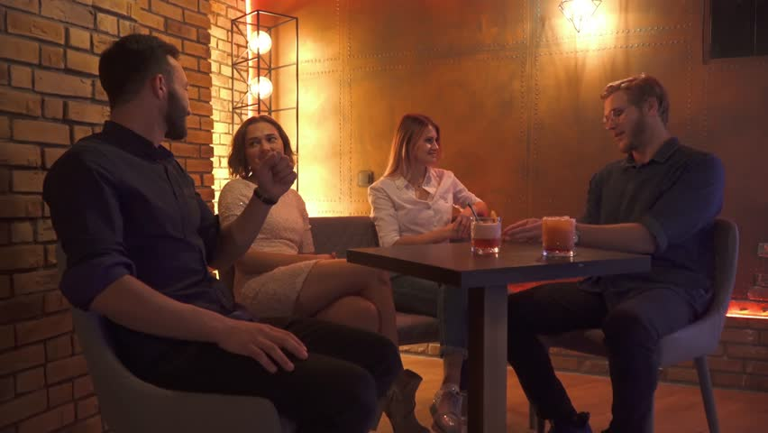 A company of friends is resting and talking at a table in a cafe. | Shutterstock HD Video #1019151142
