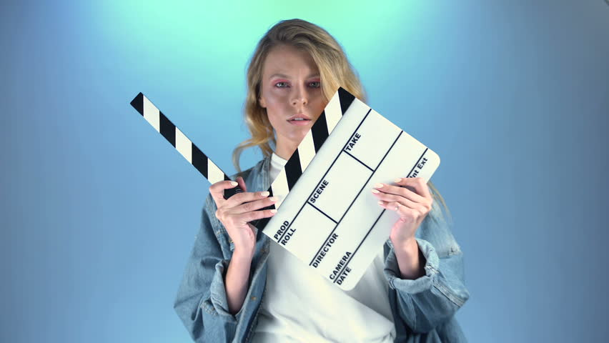 Pretty blonde actress posing for audition with movie clapper board, casting