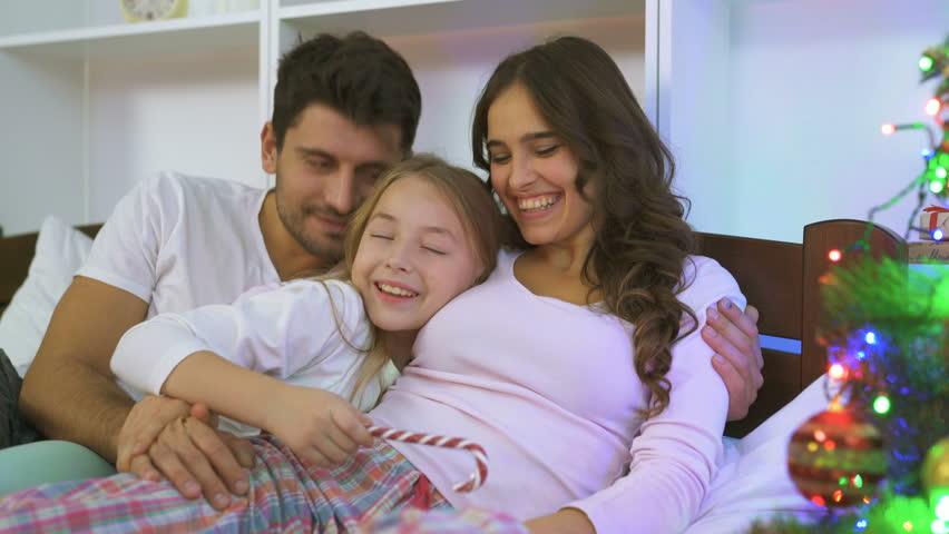 The beautiful family having fun on the bed near a christmas tree #1019168170