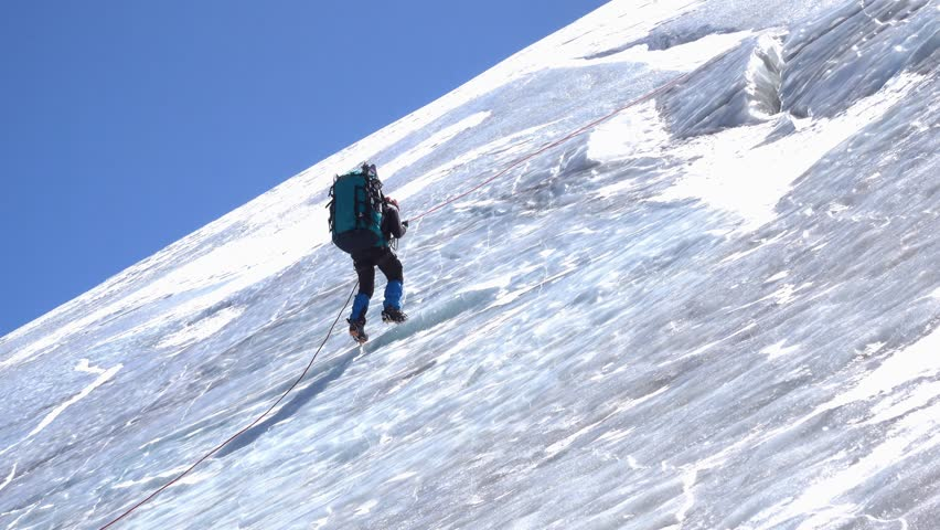 Side view of a male mountain climber going up icy slope with rope | Shutterstock HD Video #1019171794