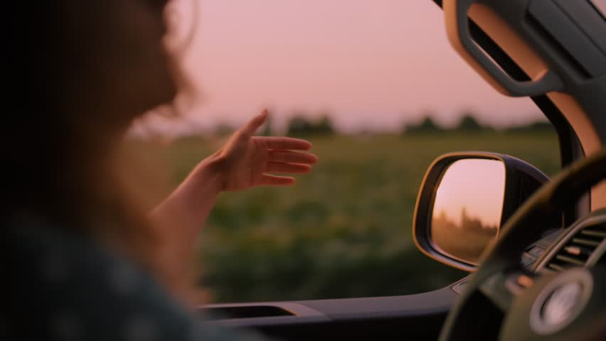 Cinematic inspirational video of young woman travelling by car or camper van, opens window to breathe fresh air of countryside, moves hand in wind. Sings melody of song, summertime vacation vibes
