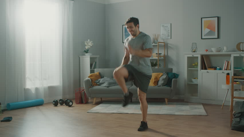 Strong Athletic Fit Man in T-shirt and Shorts is Energetically Jogging in Place at Home in His Spacious and Bright Living Room with Minimalistic Interior. #1019180734