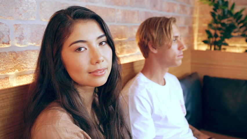 Asian girl looks at camera laughing while sitting with millennial friend waiting in restaurant in Australia during the day. Medium to closeup shot with 4K RED camera.