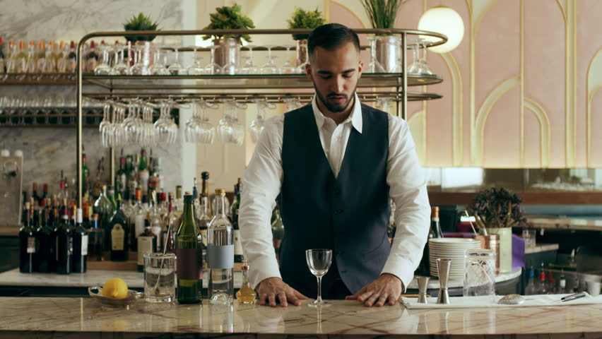 Bartender mixologist combining ingredients and making a Martini cocktail in a beautiful modern trendy bar. Medium close on a RED camera.