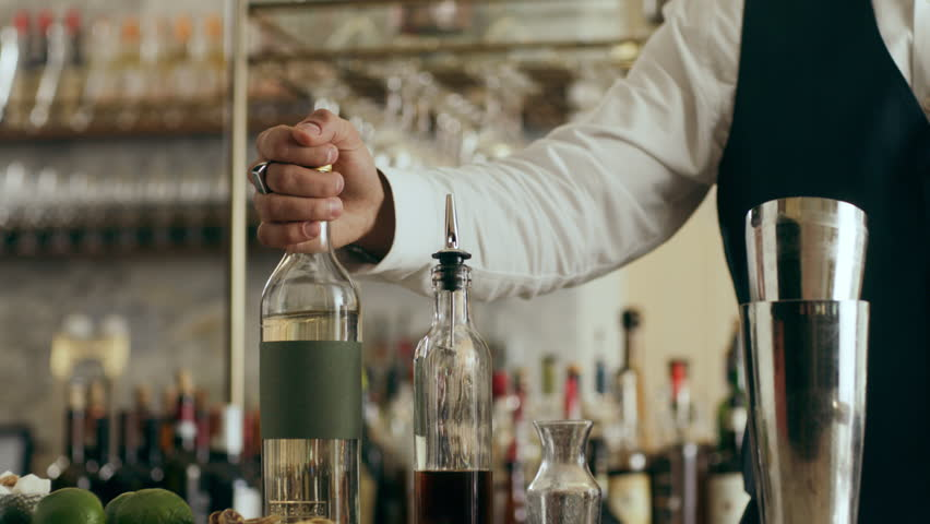 Professional flair artist flipping a bottle in the air before pouring it into shaker making classic Daiquiri cocktail in a beautiful modern trendy bar. Close shot on a RED camera.