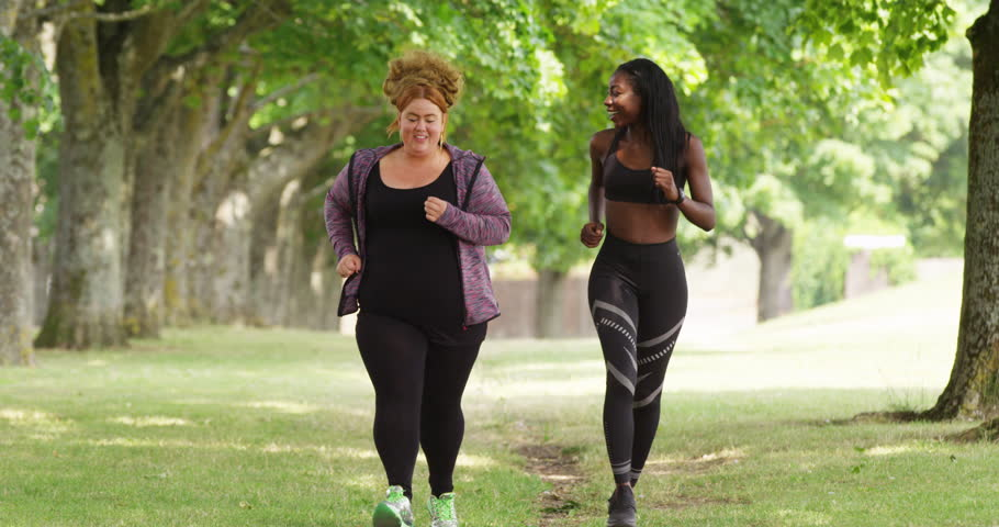 4K Slim girl with happy overweight friend getting fit & running in the park Royalty-Free Stock Footage #1019204509