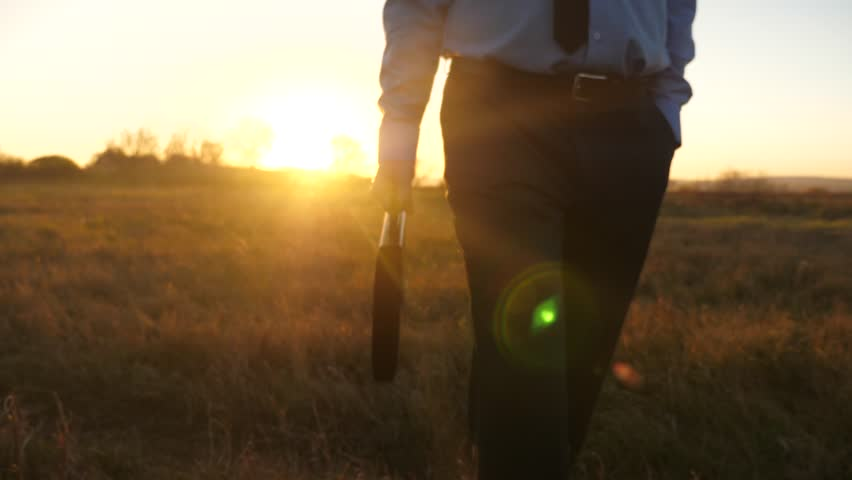 Business man with briefcase in hand and in business suit goes at sunset in glare of sun. Close-up. | Shutterstock HD Video #1019207347