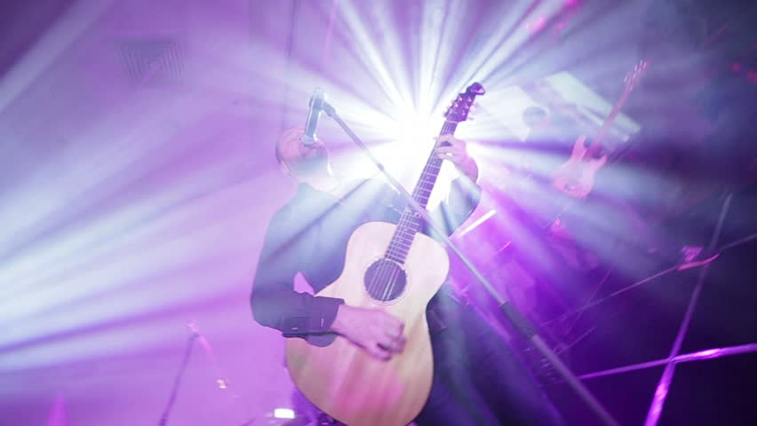 Rock concert. Artists in a brightly lit stage. Close-ups of musical instruments. Guitar, synthesizer, drums. The vocalist sings while playing the acoustic guitar. | Shutterstock HD Video #1019226016