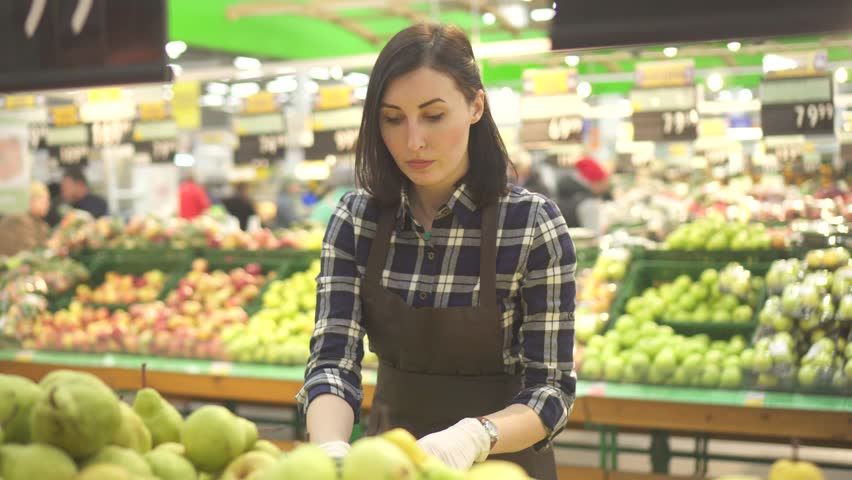 Young woman store worker in a brown apron at the department with fruits and vegetables | Shutterstock HD Video #1019227003
