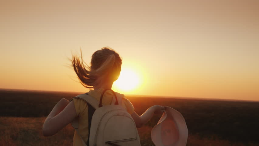 The girl joyfully waves her hat and runs towards the setting sun. Behind her backpack is a hello summer #1019237965