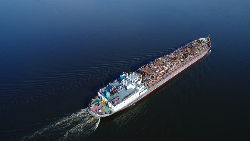 Aerial view. A barge loaded with scrap metal and waste floating on a water surface. Transportation of recyclable materials by means of a dry cargo ship.