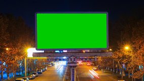 A billboard with green chroma key on a background of a city night landscape of fast moving cars with long exposure. Time Lapse video.