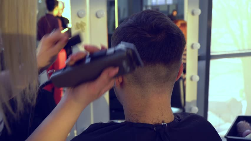 Beauty saloon. Barbershop. Stylist makes haircut to a young handsome guy. The guy sits in a chair and looks in the mirror. He is pleased. The stylist uses an electric shaver. Close-up. | Shutterstock HD Video #1019282026