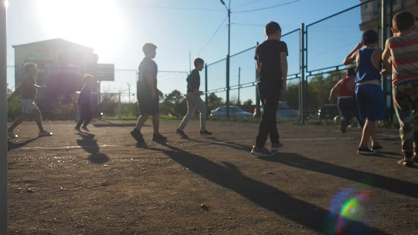 Children Training Playing Football In Ghetto. Authentic video real people kids play soccer outdoor. Football game on ghetto streets.