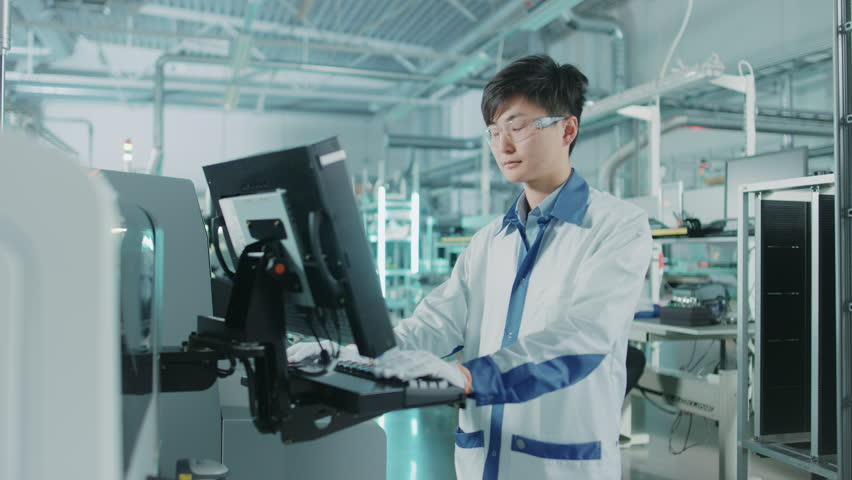On High Tech Factory Asian Engineer Uses Computer for Programming Pick and Place Surface Mount Electronic Machinery for Printed Circuit Board Assembly Line.Shot on 4K (UHD) Camera