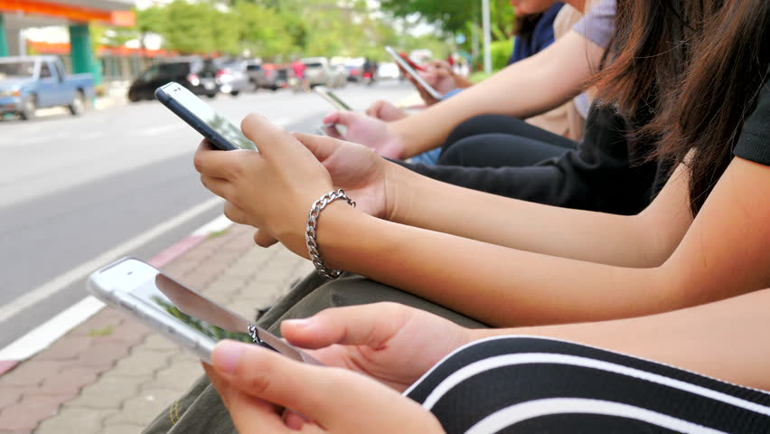 Group of friends using cellphones - Students sitting in a row and typing on the smartphones.