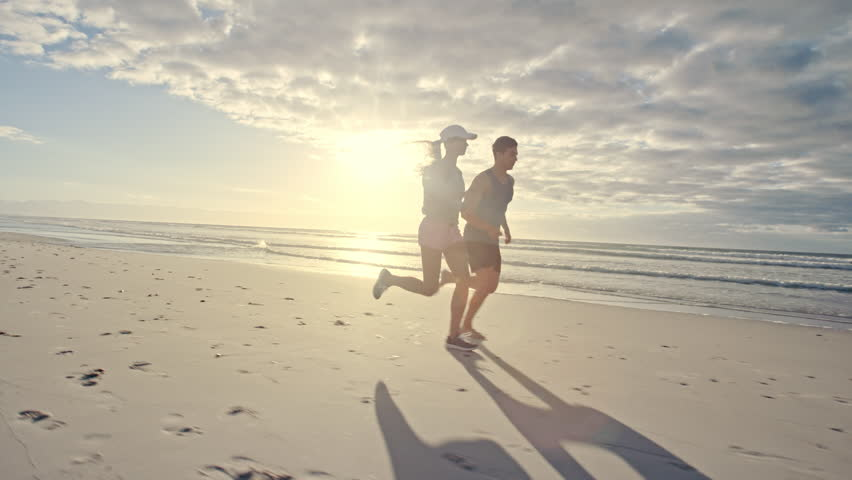 Fit young man and woman running on the beach. Young couple jogging on the sea shore.  | Shutterstock HD Video #1019329849