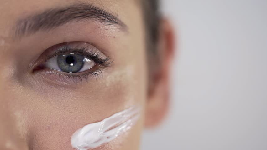 Young pretty woman applies face cream on her cheekbones, applying cream in circular motions, skin care, natural cosmetics, face care | Shutterstock HD Video #1019332702