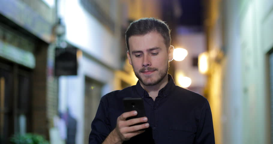 Front view portrait of a serious man walking towards camera browsing smart phone content in the night in the street