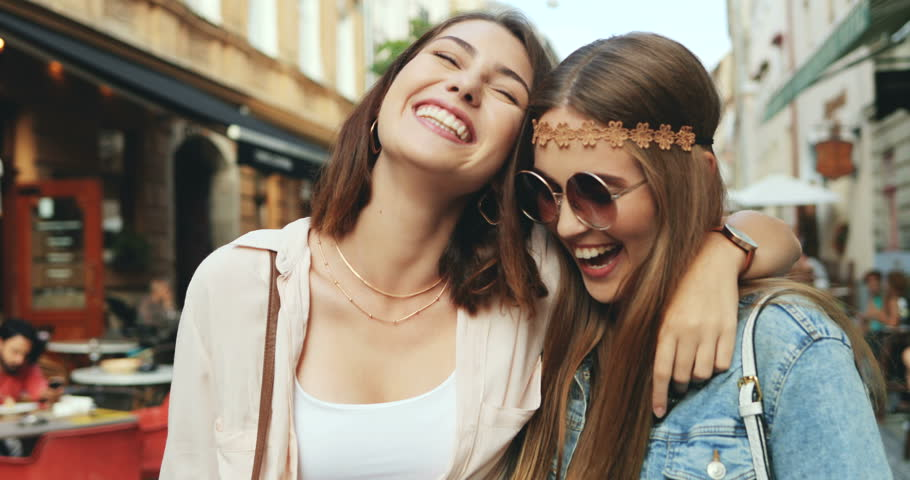 Close up of two cheerful stylish and friendly Caucasian girls walking the city street full of cafes and laughing together. Outside.