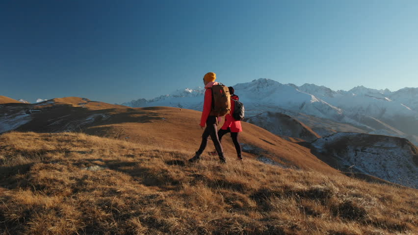 Aerial view of a two girls traveler with backpacks and cameras stroll through the hills between the epic rocks in the mountains. Girls photographers with their cameras at sunset | Shutterstock HD Video #1019350996