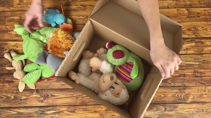 Woman is preparing to donate unwanted toys to charity shop, top view video Royalty-Free Stock Footage #1019358160
