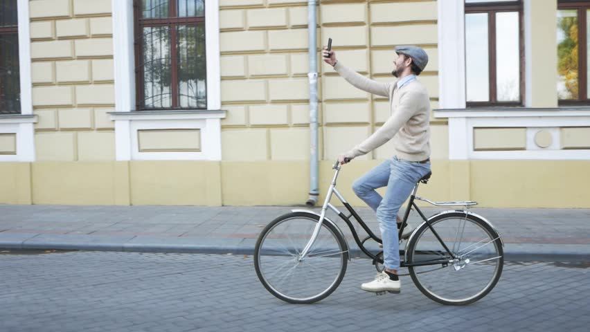Young stylish male with retro bicycle riding on the streets in sunny day, portrait modern businessman with cellphone | Shutterstock HD Video #1019363896