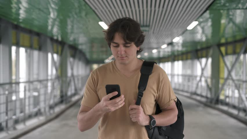 Attractive young caucasian man wearing beige t shirt and backpack is walking in tunnel, smiling and talking on smartphone. Tracking real time medium shot #1019385547
