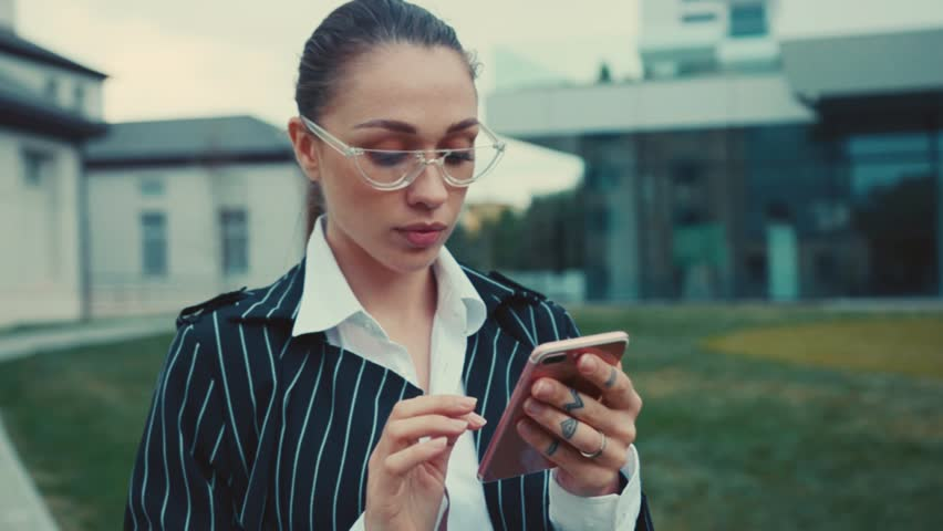 Camera moves around young businesswoman with glasses stand on street near business center and using modern smartphone smile lady elegant outside mobile cellphone close up | Shutterstock HD Video #1019385706