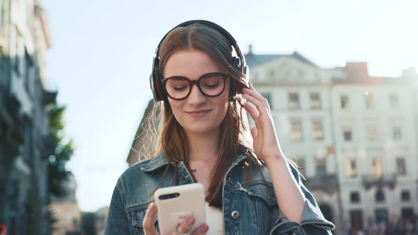 Attractive young woman with glasses listening to music in headphone use smartphone at city walk sunset look around smile portrait close up slow motion #1019386018